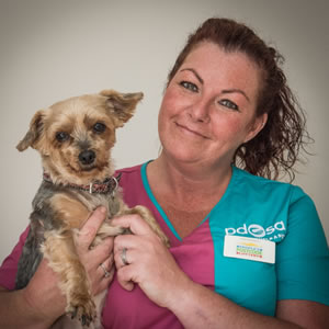 Tina, PDSA Community and Education Vet Nurse, holding a little terrier dog.