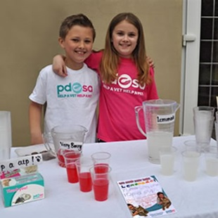Two young people wearing PDSA t-shirts at one of our events.