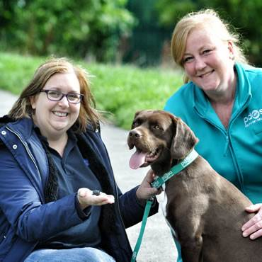 Milton, a brown Springer Spaniel crossbreed, sits next to his owner, Janice Latreche, and PDSA Vet Nurse Kylie Jones who taught the First Aid course that saved Milton's life.