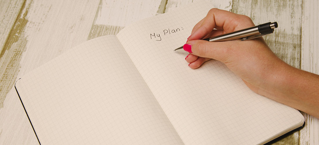 Close up of someone writing an event plan